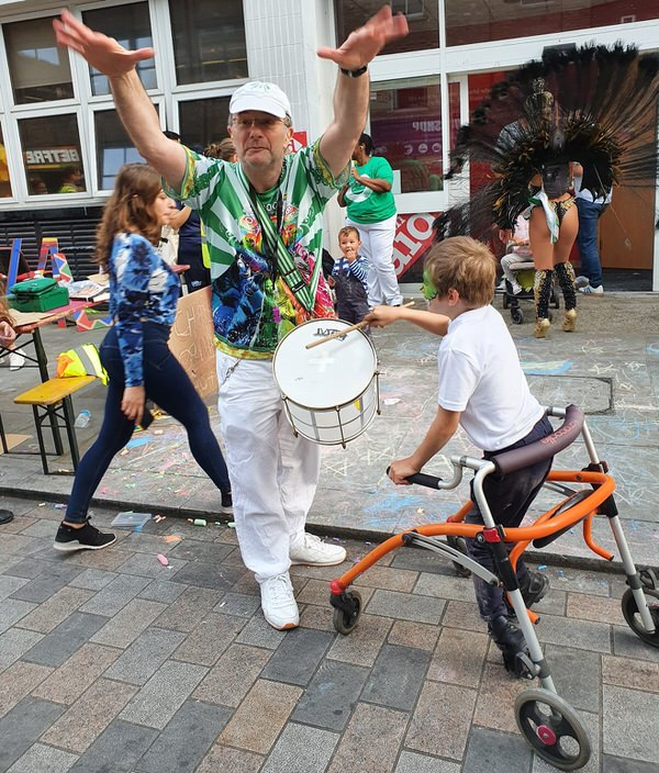 Waterloo Carnival 2021 - London School of Samba - Mestre Mags with a disabled boy leading the bateria playing Hepinique
