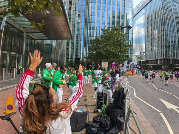 The London School of Samba performing at the London Marathon 2021 - photo of the dancers and drummers playing to the runners at Canary Wharf